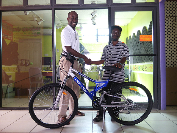 Allan Providence (left) hands over the Bike to Eric on behalf of Brian Price.